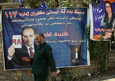A man walks by a campaign poster for the Gorran party in September 2013. (AFP/Ahmad al-Rubaye)