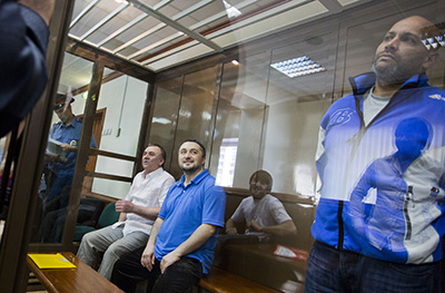 Three of the defendants--from left, Lom-Ali Gaitukayev, Rustam Makhmudov, and Sergei Khadzikhurbanov--in Moscow's City Court. (AFP/Evgeny Feldman)