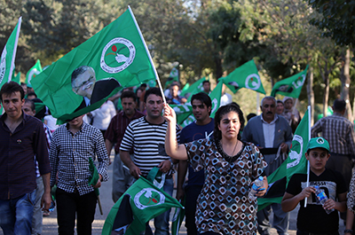 مواطنون أكراد يلوحون برايات تحمل صور الرئيس العراقي وزعيم الحزب الديمقراطي الكردستاني، جلال الطالباني، أثناء الانتخابات التي جرت في سبتمبر/أيلول 2013. (وكالة الأنباء الفرنسية/ أحمد الربيعي)