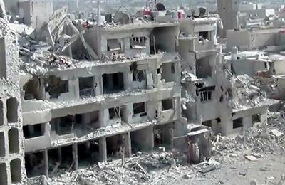 Uma imagem feita pela Shaam News Network, uma organização de notícias cidadã baseada em Damasco, mostra edifícios danificados por bombardeio pesado.(AP/Shaam News Network)