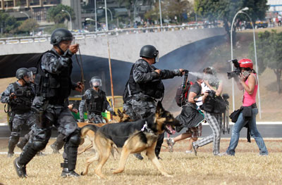 A police officer aims pepper spray at photographers during a protest in September 2013. (Reuters/Ueslei Marcelino)