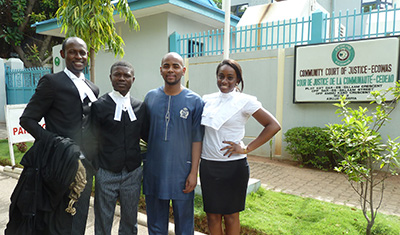 The son of the late journalist Deyda Hydara, in blue, stands outside the ECOWAS court with his lawyers. (CPJ/Peter Nkanga)