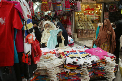 People buy garments ahead of the Eid al-Fitr holiday in Peshawar, Pakistan, on Thursday. (AP/Mohammad Sajjad)