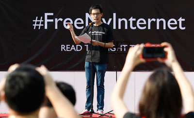 Blogger Roy Ngerng, shown at a June 2013 protest against licensing regulations on news websites, has been fired from his job in health-care since being accused of defamation by the prime minister. (Reuters/Edgar Su)