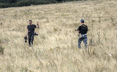 An armed separatist orders a journalist to leave the area near the crash site of the Malaysia Airlines plane in Donetsk region. (AFP/Bulent Kilic)
