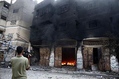 A journalist films a burning building in Gaza's Shijaiyah district on July 20. (AFP/Thomas Coex)