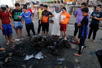 People gather at the site of a bomb attack at a market in Baghdad's Sadr City on Wednesday. (Reuters/Wissm al-Okili)