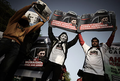 Bahraini photographers hold up placards in solidarity with freelance photojournalist Ahmed Humaidan, who was sentenced to 10 years in prison. (AFP/Mohammed al-Shaikh)