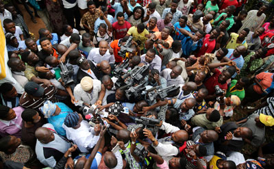 Journalists surround a politician at the start of the Osun state governorship election in southwest Nigeria on August 9, 2014. (Reuters/Akintunde Akinleye)