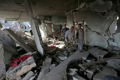 Palestinians search the rubble of their family house which was hit by an Israeli strike in Beit Hanoun, in the northern Gaza Strip. (AP/Adel Hana)