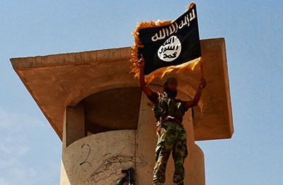 An Islamic State militant stands with the Islamist flag in Iraq. (AFP/Welayat Salahuddin)