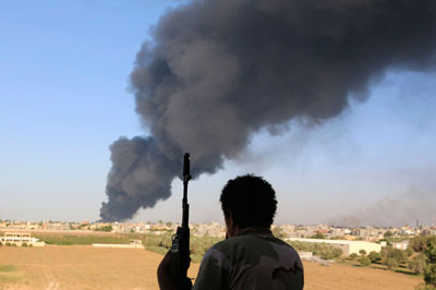 A fighter watches as smoke rises after rockets fired by one of Libya's militias struck a fuel tank in Tripoli on August 2. (Reuters/Hani Amara)
