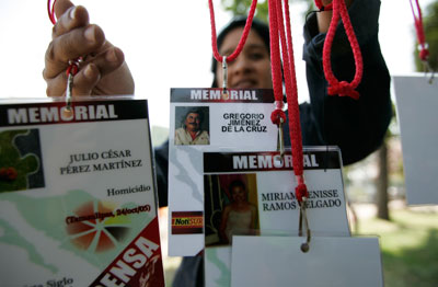 A woman hangs accreditations of journalists killed in recent years while covering the news in Mexico, at a protest in Guadalajara on February 23, 2014. (Reuters/Alejandro Acosta)