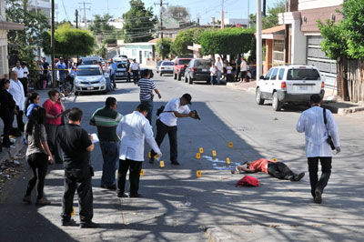In this May 12, 2014 photo, forensic workers examine the scene where an activist for missing persons was gunned down by unknown assailants in Culiacan, Mexico. (AP/El Debate, Dulce Mercado)
