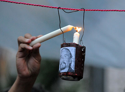 A candle is lit at a 2012 vigil for more than 20 journalists killed in Honduras over three years. (AFP/Orlando Sierra)