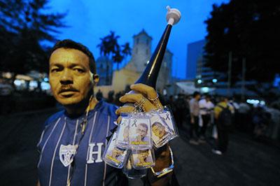 A man sells keychains showing murdered Honduran radio host Ángel Alfredo Villatoro. (AFP/Orlando Sierra)