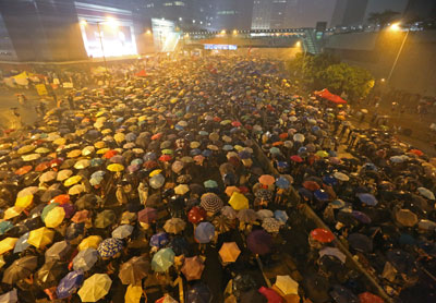 Pro-democracy protesters hold umbrellas under heavy rain in a street near the government headquarters in Hong Kong late on Tuesday, September 30. (AP)