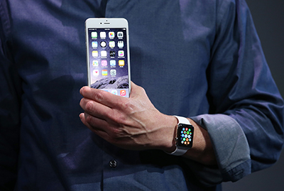 Apple chief executive Tim Cook reveals the iPhone 6 and Apple Watch in September. Apple's latest software includes automatic encryption. (Getty Images/AFP/Justin Sullivan)