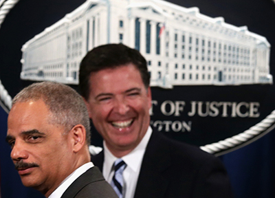FBI Director James B. Comey, pictured right with outgoing Attorney General Eric Holder in June, says FBI efforts to fight crime are being thwarted by moves to protect user privacy. (Alex Wong/Getty Images/AFP)