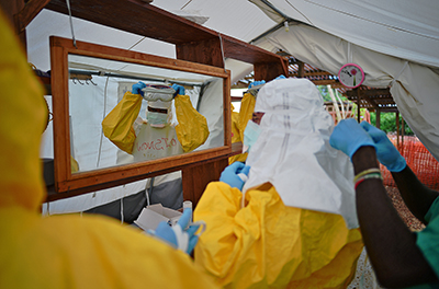 Health workers in Sierra Leone put on protective clothing. The government there has joined forces with the press to raise awareness about Ebola. (AFP/Carl de Souza)