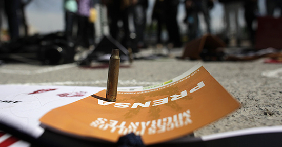 A bullet shell is seen standing on press accreditation, surrounded by journalists protesting the murder of reporters in Mexico. (Reuters/Daniel Becerril)