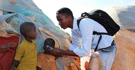 Somali journalist Yusuf Ahmed Abukar, seen here speaking to internally displaced children, was killed by a car bomb in 2014. (Abdukhader Ahmed)