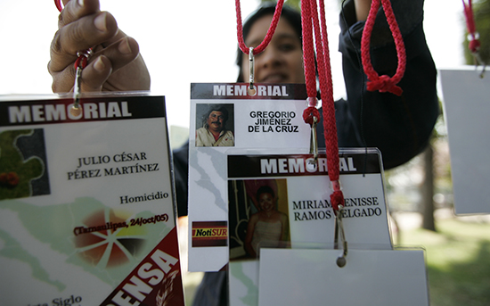 A woman holds up press IDs with the names of journalists killed in Mexico. (Reuters/Alejandro Acosta)