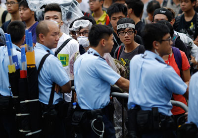 Police officers face off with protesters blocking the entrance to Hong Kong's Chief Executive Leung Chun-ying offices on Thursday. (Reuters/Carlos Barria)