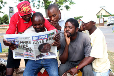 Taxi drivers read the news of President Michael Sata's death in The Post special edition on October 29, 2014 in Lusaka. (AFP/Chibala Zulu)