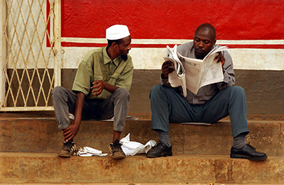 Two men read a paper in Kigali. Accreditation is voluntary for Rwandan journalists but many say it is difficult to work without a press card. (AFP/Marco Longari)