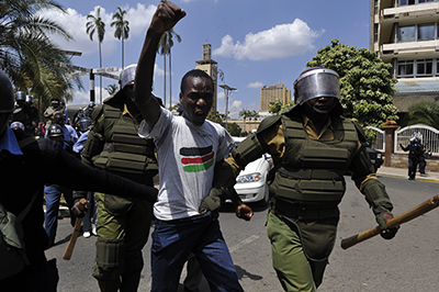 Police arrest one of the protesters who gathered in Nairobi on December 18 to oppose the security bill. (AFP/Simon Maina)