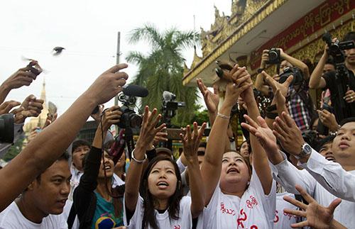 Journalistes birmans libèrent des oiseaux en devant d'une pagode en solidarité avec cinq journalistes qui ont été condamnés a des peines de prison à 10 ans de travaux forcés en juillet.