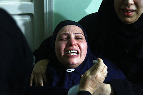 The mother of Egyptian journalist Mayada Ashraf mourns at her funeral. Ashraf was shot dead while covering clashes in eastern Cairo. (AFP/Ahmed Mahmoud)