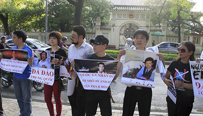 Protesters in Hanoi hold up pictures of jailed bloggers and activists in May 2014. Hopes that authorities would end the repression of bloggers have faded with the arrest of three more writers. (Reuters/Nguyen Huu Vinh)