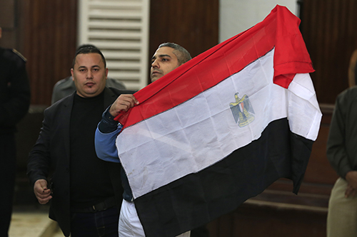 Mohamed Fahmy holds an Egyptian flag on February 12 after a court ruled he and Al-Jazeera colleague Baher Mohamed could be released on bail. (AP/Hassan Ammar)