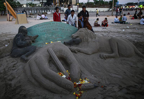 A sand sculpture in Mumbai for victims of the Charlie Hebdo attack. An editor arrested after complaints over her decision to publish an image of the French magazine's cover has gone into hiding in India. (Reuters/Danish Siddiqui)