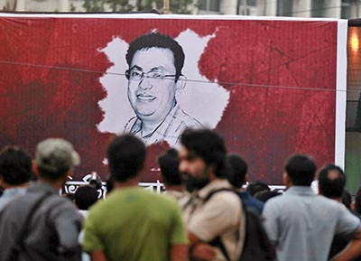 Protesters in Dhaka gather around the portrait of Avijit Roy, a blogger who was killed on Thursday. (AP/A.M. Ahad)
