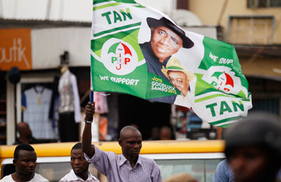 A man holds a flag in support of Nigerian President Goodluck Jonathan at a campaign rally in Ikeja district in Lagos February 3. (Reuters/Akintunde Akinleye)
