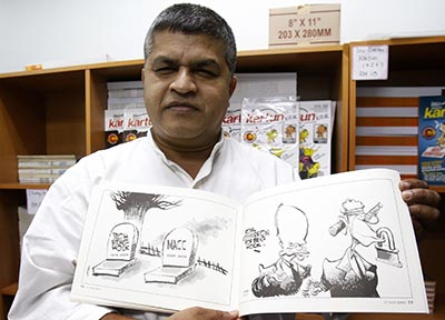 Zunar holds a copy of his banned cartoon book in 2010. The cartoonist has been arrested on accusations of sedition. (AP/Lai Seng Sin)