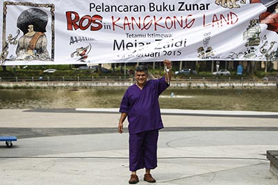 Malaysian cartoonist Zunar poses in plastic handcuffs prior to the launch of his new book of political cartoons. (AP/Joshua Paul)