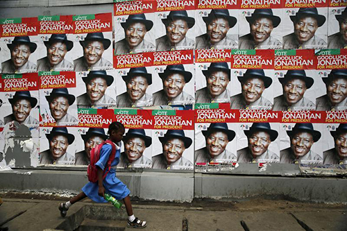 A schoolgirl walks past campaign posters for Nigerian President Goodluck Jonathan in Lagos. Journalists covering the election campaign say they are being attacked. (Reuters/ Akintunde Akinleye)