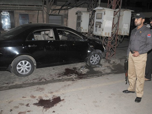 A police officer stands guard next to the car Pakistani journalist Raza Rumi was in when gunmen opened fire on him and killed his driver, Mustafa, in March 2014. (Tariq Hasan/Express Tribune)