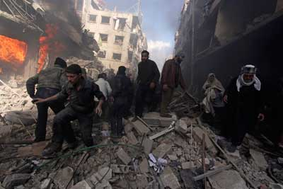 People walk on rubble after what activists said were airstrikes and shelling by forces loyal to Syria's President Bashar al-Assad in the Douma neighborhood of Damascus, February 9, 2015. (Reuters/Mohammed Badra)
