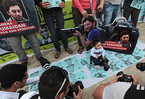 The infant son of Ahmed Humaidan is surrounded by fliers at a rally for the jailed journalist in 2014. The photographer is one of at least five journalists held in Jaw Prison. (AP/Hasan Jamali)