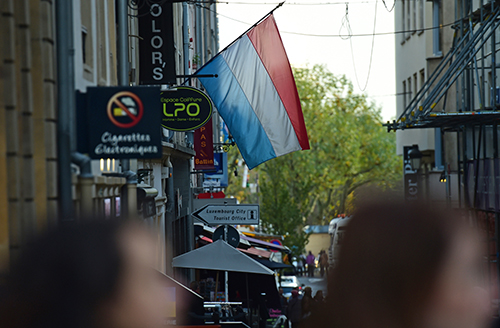 A flag flutters over a Luxembourg city street, above. French journalist Edouard Perrin, who helped expose the LuxLeaks tax revelations, has been indicted in the country. (AFP/Emmanuel Dunand)