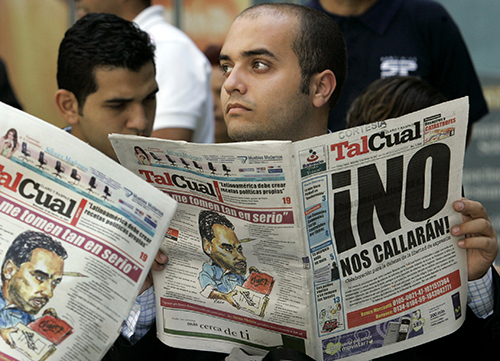 Copies of Tal Cual are read in Caracas in 2007. The critical Venezuelan newspaper has been forced to downsize in an effort to survive. (AP/Leslie Mazoch)