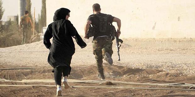 Uma repórter corre juntamente com um combatente rebelde, fugindo de atiradores perto de Aleppo, na Síria, 10 de outubro de 2014. (Reuters/Jalal Al-Mamo)