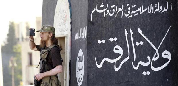 مقاتل يستخدم هاتفاً خلوياً لتصوير رفاقه من مقاتلي تنظيم الدولة الإسلامية أثناء استعراض عسكري في شوارع مدينة الرقة السورية في 30 يونيو/حزيران 2014. (رويترز)