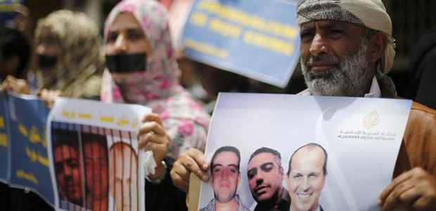 Journalists protest the imprisonment in Egypt of Al-Jazeera staffers Peter Greste, Mohamed Fahmy and Baher Mohamed outside the network's offices in Sanaa, Yemen, on June 25, 2014. (Reuters/Khaled Abdullah)