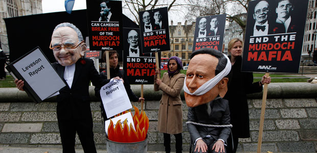 A protester in London, dressed as a caricature of News Corp. Chairman Rupert Murdoch, burns a government report on media abuses while another wearing a mask depicting Prime Minister David Cameron sits tied to a chair, November 29, 2012. (AP/Sang Tan)